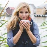Happy free blonde woman enjoying hot beverages at lakeside. Royalty Free Stock Images
