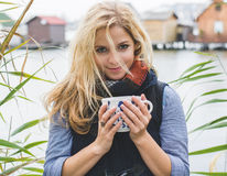 Happy free blonde woman enjoying hot beverages at lakeside. Royalty Free Stock Photos