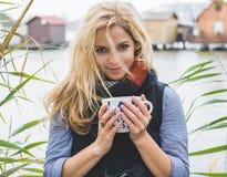 Happy free blonde woman enjoying hot beverages at lakeside. Royalty Free Stock Photos