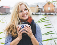 Happy free blonde woman enjoying hot beverages at lakeside. Royalty Free Stock Images