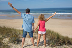 Happy free couple cheering on beach travel holiday. Rear view royalty free stock photos