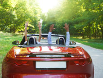Happy free couple driving in red retro car cheerin Stock Image