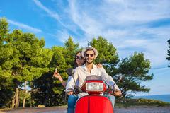 Happy free freedom couple driving scooter excited on summer holidays vacation. Young multiethnic couple Royalty Free Stock Images