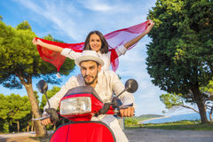 Happy free freedom couple driving scooter excited on summer holidays vacation. Young multiethnic couple Stock Photo