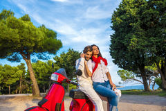 Happy free freedom couple driving scooter excited on summer holidays vacation. Young multiethnic couple Stock Photos