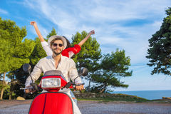 Happy free freedom couple driving scooter excited on summer holidays vacation. Young multiethnic couple Stock Photography