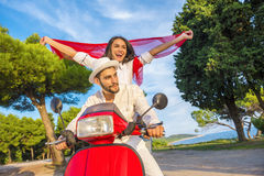 Happy free freedom couple driving scooter excited on summer holidays vacation. Stock Photos