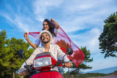 Happy free freedom couple driving scooter excited on summer holidays vacation. royalty free stock image