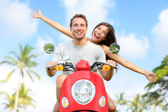 Happy free freedom couple driving scooter. Excited on summer holidays vacation. Young multiethnic couple in love, Asian woman, Caucasian man Stock Image
