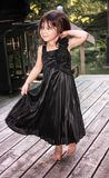 Small girl child in dress. Happy and free in her new black dress the baby girl dances and swirls her skirt Royalty Free Stock Images