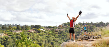 Happy free man is victorious. Happy free fun man stands victorious on a mountain with arms outstretched and helmet in hand royalty free stock photo