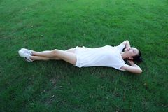 A happy free smile peace balance meditation beauty girl Asian Chinese lying laying on grass lawn thinking Royalty Free Stock Photography
