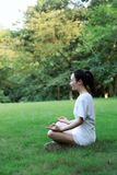 A happy free smile peace balance meditation beauty girl Asian Chinese lying laying on grass lawn thinking do yoga in forest park Stock Image