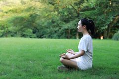 A happy free smile peace balance meditation beauty girl Asian Chinese lying laying on grass lawn thinking do yoga in forest park Royalty Free Stock Photos