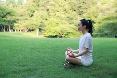A happy free smile peace balance meditation beauty girl Asian Chinese lying laying on grass lawn thinking do yoga in forest park Royalty Free Stock Images