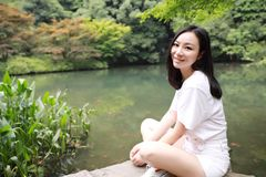 A happy free smile peace balance meditation beauty girl Asian Chinese travel hiking smell maple do yoga by lake bag hangzhou xihu royalty free stock images