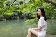A happy free smile peace balance meditation beauty girl Asian Chinese travel hiking smell maple do yoga by lake bag hangzhou xihu Stock Photos