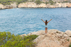 Happy free teenager raising arms on vacations Stock Photography