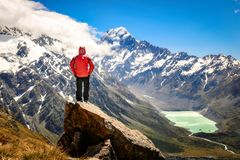 Happy free tourist man standing outstretched up looking at river and mountains landscape from Mueller Hut, MT. Cook - New Zealand royalty free stock image