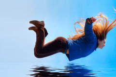 Happy free woman flying over water. Happy girl flying over blue water Stock Image