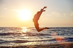 Happy free woman jumping with happiness on the beach in the sunset sun royalty free stock images