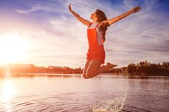 Happy and free young woman jumping and raising arms on river bank. Freedom. Active lifestyle. Summer holidays stock photography