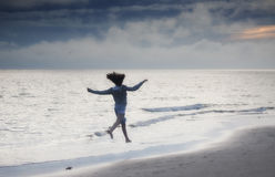 Happy freedom girl. Young girl running and jumping on the beach at sunset Stock Photos