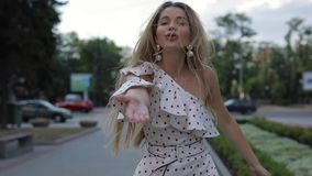 Beautiful happy woman in dress blowing air kiss at summer city, slowmotion stock footage