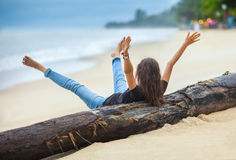 Happy freedom woman with hands up and legs up cheering on the be Stock Image