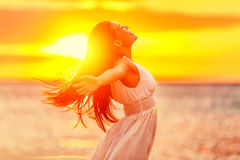 Happy freedom woman relaxing in sunshine lifestyle. Happy woman feeling free with open arms in sunshine at beach sunset. Freedom and carefree enjoyment girl Stock Image