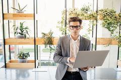 Happy freelance business man sitting on office desk with laptop in hands and typing, looking at camera. Happy smiling businessman looking at camera while sitting Royalty Free Stock Photography
