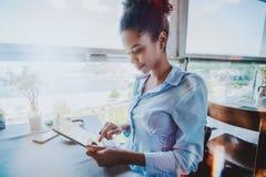 Happy freelancer girl with digital tablet in restaurant stock photos