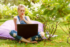 Happy freelancer working in the garden. Writing, surfing in the internet using laptop. Young woman relaxing and having Stock Images