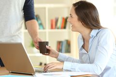 Freelancer working at home and husband giving coffee. Happy freelancer working at home and her husband giving a cup of coffee stock images