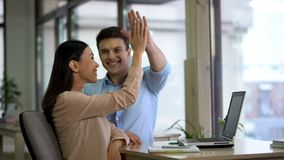 Happy freelancers giving high five and smiling, company achievement, success. Stock photo stock photo