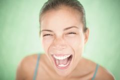 Happy fresh energetic woman. Very expressive young asian woman laughing or screaming of joy. Shallow depth of field on green background Stock Photo