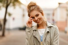 Happy fresh portrait of a young beautiful smiling woman. In a fashionable jacket in the city stock photography