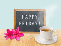 Happy Friday on chalkboard. With coffee cup and flower stock photo