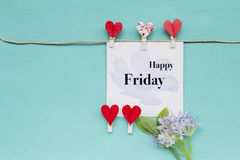 Happy Friday greeting card concept. Card with red heart clip with flower on blue background stock image