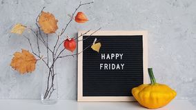 Happy Friday text on black letter board and bouquet of branches with yellow leaves on clothespins in vase on table. Template for postcard, greeting card concept stock video footage
