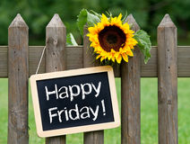 Happy Friday!. Text 'Happy Friday!' on black chalkboard hung on a wooden fence with a large yellow sunflower royalty free stock photos