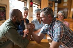 Happy friend arm wrestling each other royalty free stock photography