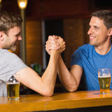 Happy friend arm wrestling each other Stock Photos