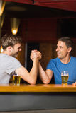 Happy friend arm wrestling each other Stock Images