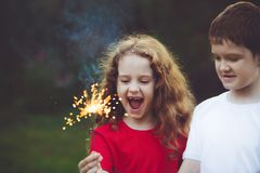 Happy friend child in party with burning sparkler in his hand. stock images