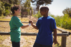 Happy friend holding hands during obstacle course. In boot camp royalty free stock images