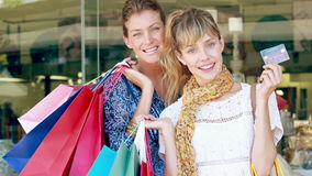 Happy friend holding shopping bag and showing credit card stock video footage