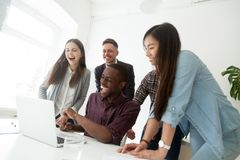 Happy friendly diverse millennial team laughing watching online. Happy friendly diverse millennial team laughing watching joke on laptop, excited multiracial Stock Image