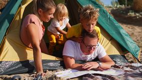 A happy and friendly family makes a plan for the route of travel on a paper map. A young family who came to rest create a route for their travel, they look at stock video footage