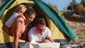 A happy and friendly family makes a plan for the route of travel on a paper map. A young family who came to rest create a route for their travel, they look at stock video